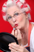 Grandmother with her hair in rollers applying lipstick